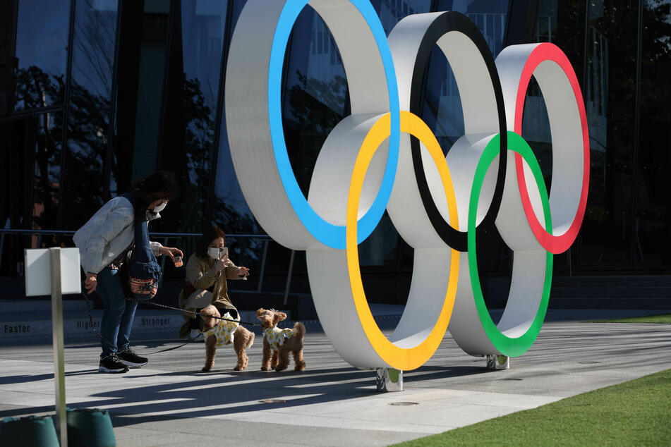Eine Frau fotografiert Hunde an den Olympischen Ringen im Bezirk Shinjuku. Aufgrund der Corona-Pandemie dürfen dieses Jahr keine ausländischen Fans nach Japan reisen.