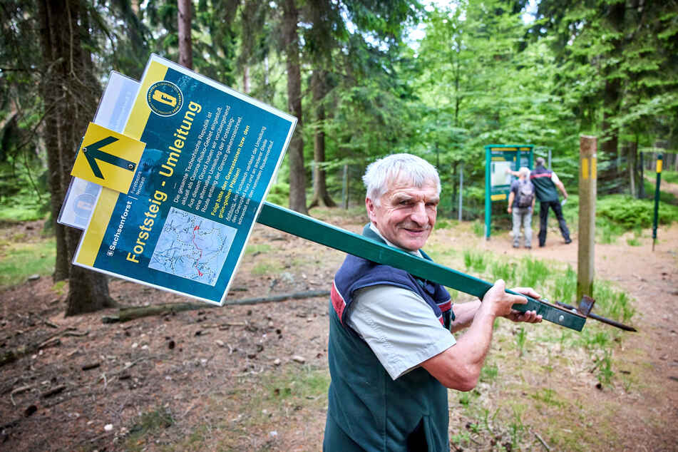 Cunnersdorf bei Königstein: Forststeig-Ranger Wolfram Claus trägt ein abgebautes Hinweisschild. Der nach Tschechien führende Wanderweg Forststeig ist nach Aufhebung der Einschränkungen während der Corona-Pandemie wieder durchgängig offen.