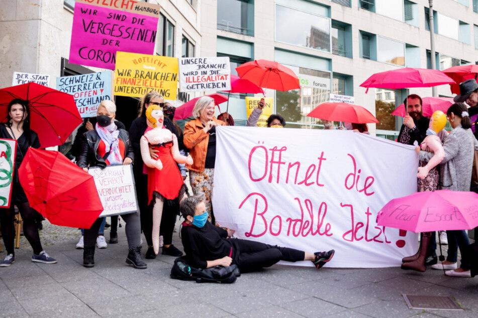 Teilnehmerinnen und Teilnehmer einer Protestaktion für die Öffnung von Prostitutionsstätten stehen nahe des Bundesrates auf einem Bürgersteig