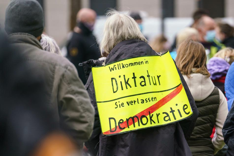 """Eine Demonstrantin steht bei einer Kundgebung der """"Querdenken""""-Bewegung in Wiesbaden. Der Verfassungsschutz schaut nun genauer hin."""