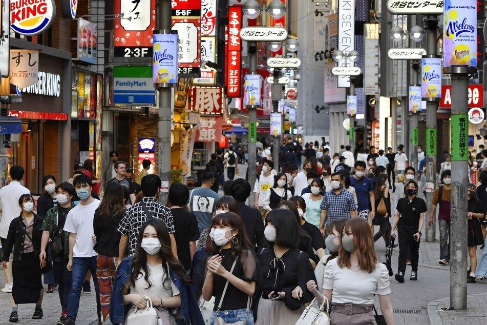 Zahlreiche Passanten mit Mundschutz gehen auf einer Straße. Das vergangenen Wochenende war das erste Wochenende, nachdem Japan den Notstand, den das Land aufgrund der Corona-Krise ausgerufen hatte, vorzeitig aufgehoben hat.