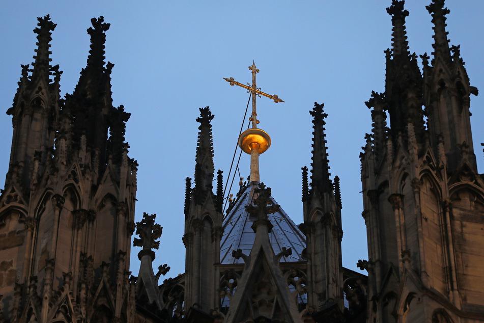 Ein goldenes Kreuz auf dem Kölner Dom: Nach Monaten der öffentlichen Kritik hat die katholische Kirche einer Umfrage zufolge massiv an Glaubwürdigkeit eingebüßt.