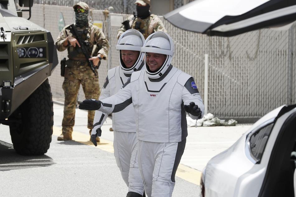 """Die NASA-Astronauten Douglas Hurley (l.) und Robert Behnken, lächeln, während sie das Neil Armstrong Operations and Checkout Building auf ihrem Weg zur Startrampe 39A verlassen, an der eine """"Falcon 9""""-Rakete zum Start bereit steht."""