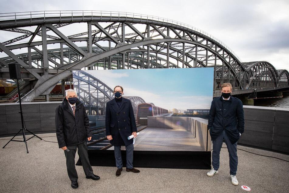 Jürgen Bruns-Berentelg (l-r), Henrik Falk und Anjes Tjarks stehen bei einer Pressekonferenz zum Start der Planungen für die Verlängerung der U4 an der Station Elbbrücken.