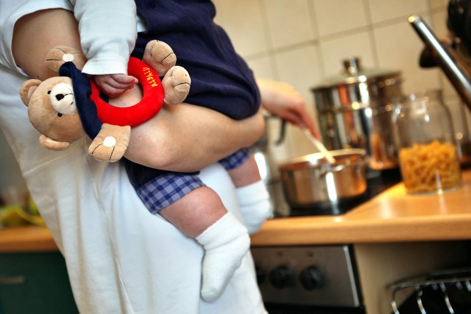 Eine Mutter mit Kleinkind beim Kochen. (Archivbild)