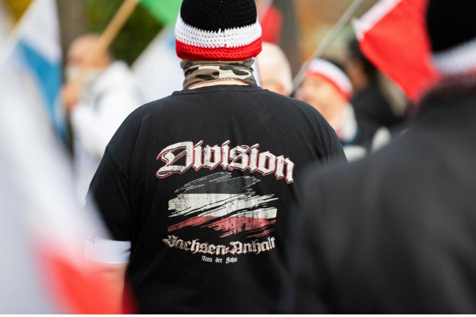 """Ein Mann trägt bei einer Demonstration von Reichsbürgern einen Pullover mit dem Aufdruck """"Division Sachsen-Anhalt - Treu der Fahne'""""."""