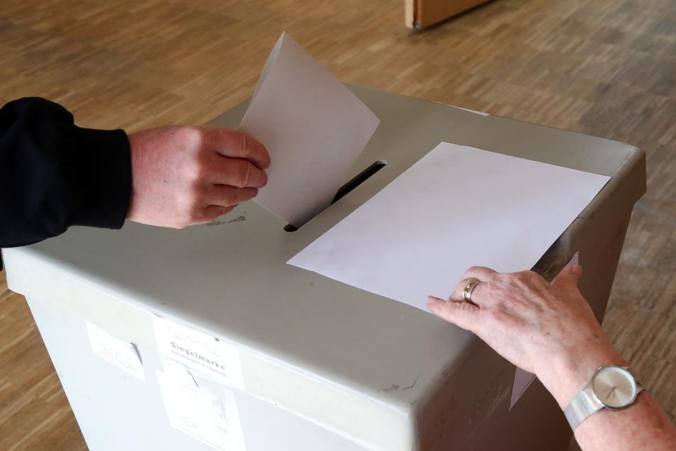 Eine Wählerin wirft ihren Wahlschein in einem Wahllokal in die Wahlurne.