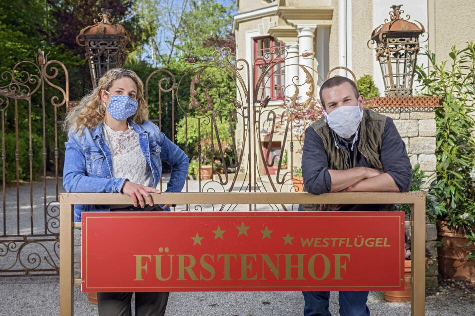 """Die """"Sturm der Liebe""""-Hauptdarsteller posieren vor dem Eingang des Fürstenhofs."""