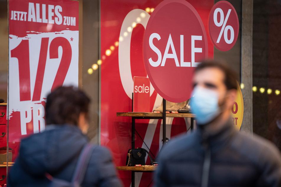 Passanten gehen an einem Schuhgeschäft vorbei, das am letzten Tag vor dem Lockdown mit Ausverkauf und Rabatten von 50 Prozent wirbt. (Archivbild)