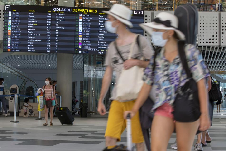 Reisende mit Schutzmasken gehen an einer Tafel mit den Abflugzeiten in einem internationalen Flughafen vorbei.
