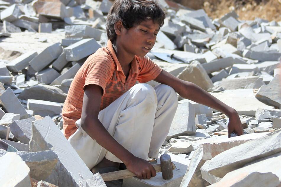 Ein kleiner Junge sitzt in der indischen Provinz Rajasthan mit einem Hammer auf Marmorsteinen. Tausende Kinder hauen in indischen Steinbrüchen Steine für den europäischen Markt.