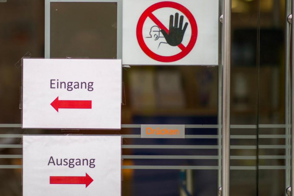 """""""Eingang"""" und """"Ausgang"""" sowie ein Durchgangsverbot stehen auf Schildern am Eingang zu einer Bank in der Nürnberger Innenstadt."""