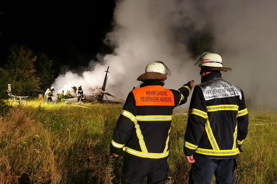 Feuerwehrleute stehen am Einsatzort in Lemsahl-Mellingstedt.
