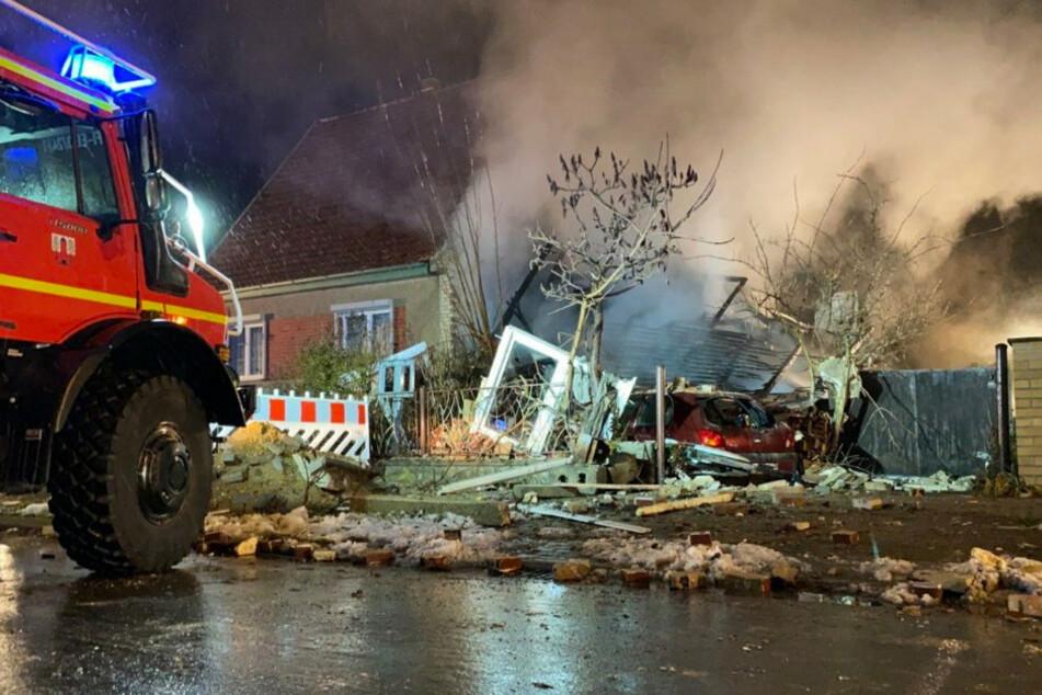 Ein Einsatzfahrzeug der Feuerwehr steht vor einer zerstörten Doppelhaushälfte in Finsterwalde.
