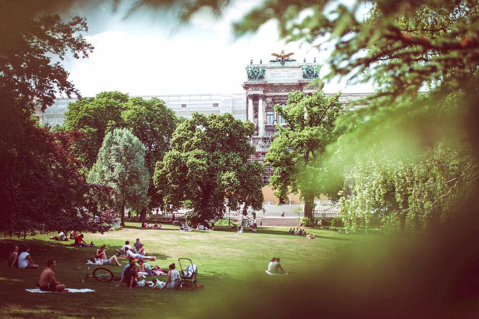 Österreicher und Touristen entspannen vor der Neuen Burg im Stadtzentrum Wiens.