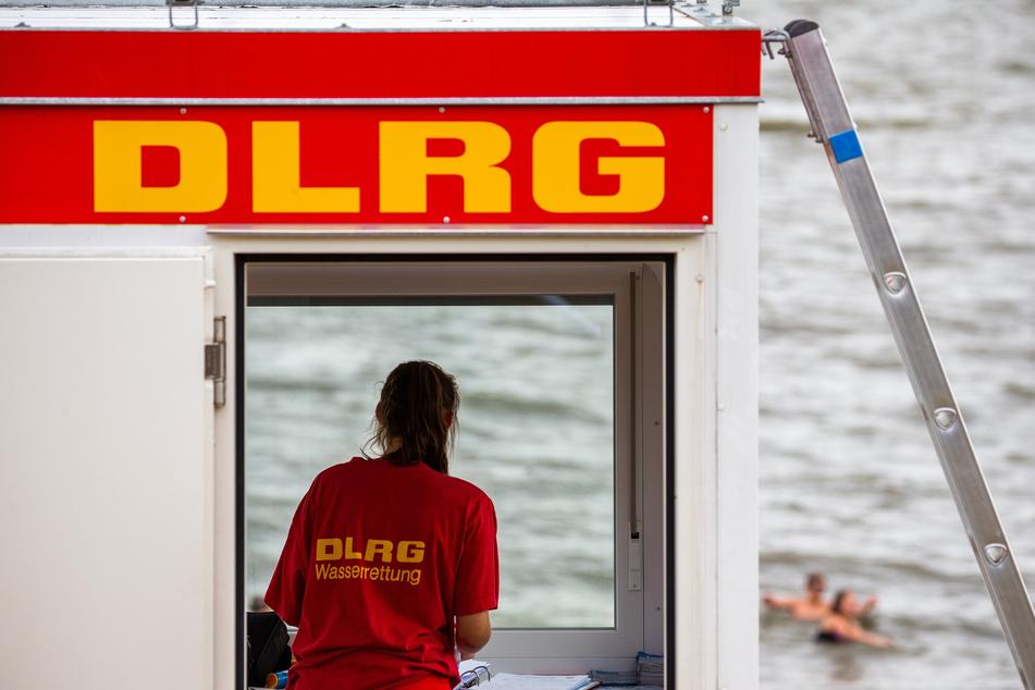 Eine Rettungsschwimmerin der DLRG (Deutsche Lebens-Rettungs-Gesellschaft) steht vor dem Fenster eines Wachturms am Südstrand in Wilhelmshaven.