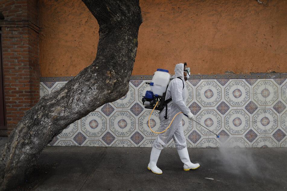 Ein Arbeiter in Mexiko-Stadt versprüht Desinfektionsmittel auf einer Straße gegen das neue Coronavirus.