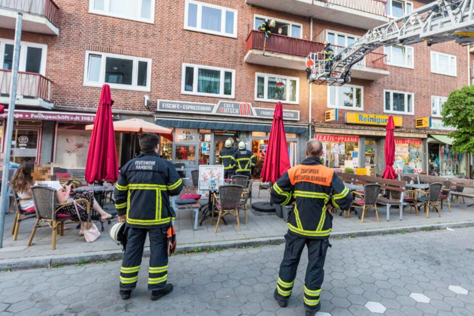 Einsatzkräfte begutachten den bröckelnden Balkon über der Terrasse des Eis-Cafés.