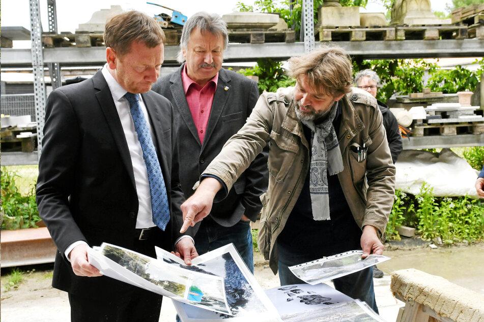 Steinbildhauermeister Schubert (r.) zeigt MP Kretschmer und Gablenz-Bürgermeister Dietmar Noack (66, CDU) historische Aufnahmen der Rakotz-Grotte.