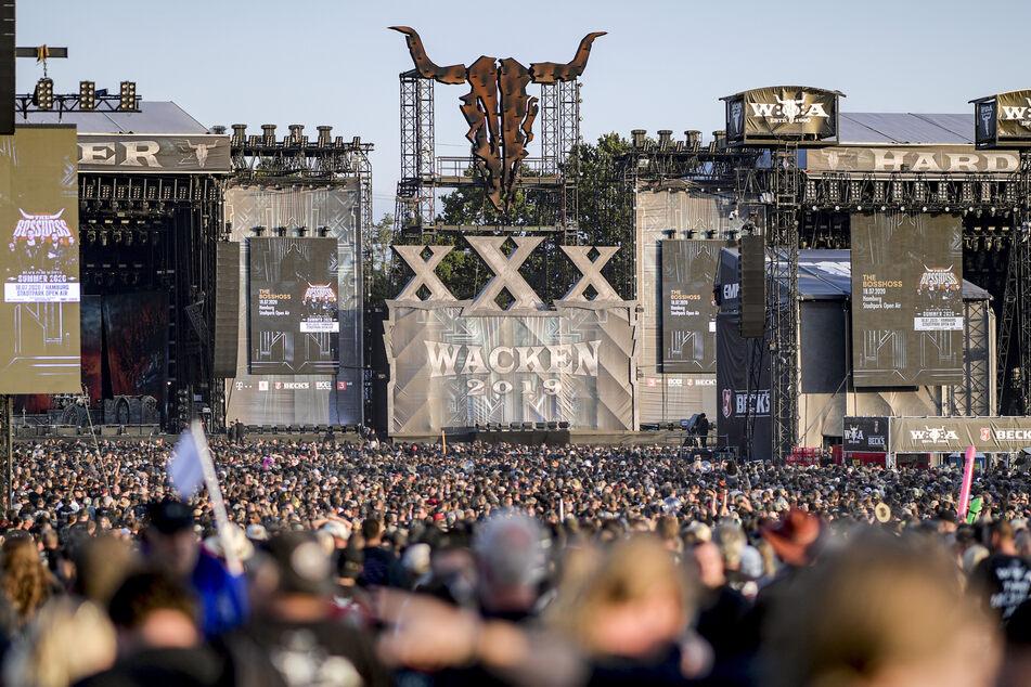 Festivalteilnehmer des WOA (Wacken Open Air) feiern vor den Bühnen.