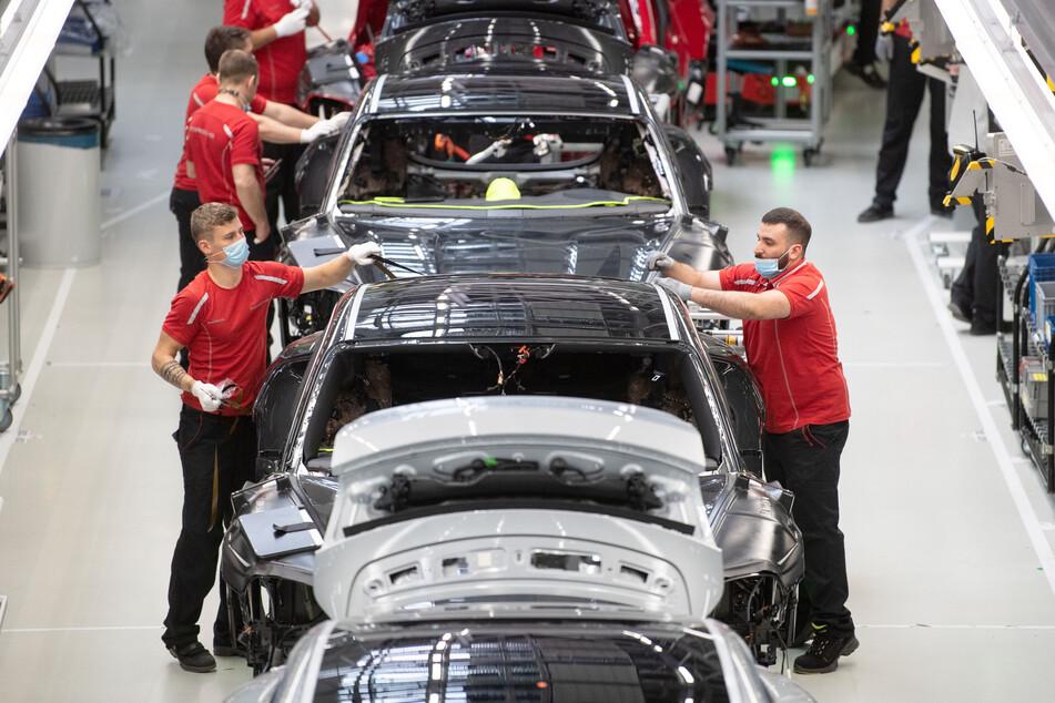 Stuttgart: Mitarbeiter der Porsche AG tragen bei der Produktion des elektrisch angetriebenen Sportwagens Porsche Taycan Mundschutz.