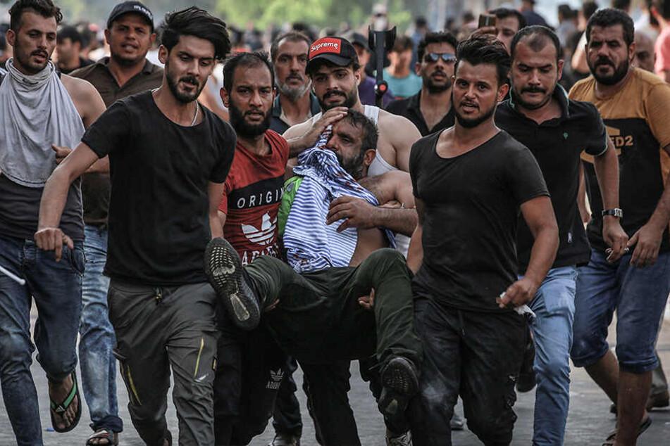 Demonstranten bringen einen verletzten Mann in Sicherheit.