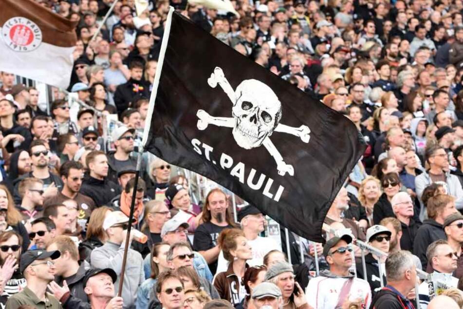 Ein Fan schwenkt eine Fahne mit dem Totenkopf-Logo.