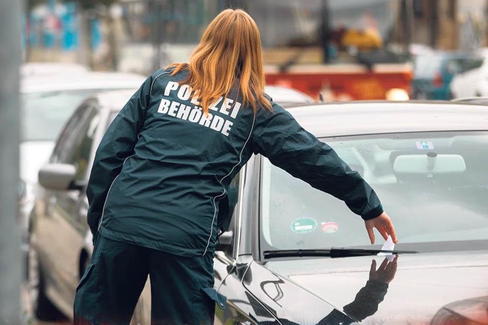 Eine Politesse klemmt ein Knöllchen unter den Scheibenwischer. In Leipzig, Dresden und Zwickau wird jetzt auch nachts gegen Falschparker hart durchgegriffen.