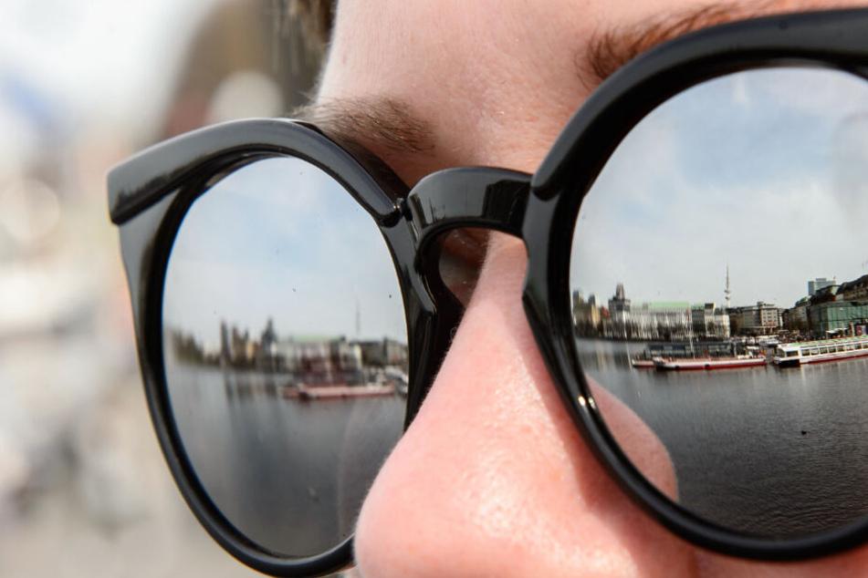 In den Gläsern einer Sonnebrille spiegelt sich die Binnenalster. Am Wochenende solltet Ihr unbedingt an dieses Accessoir denken.