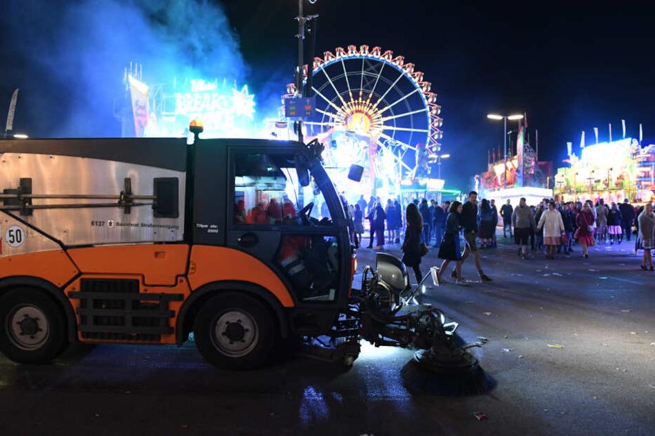 Ein Kehrfahrzeug der Stadtreinigung fährt bei Dunkelheit am Riesenrad vorbei.