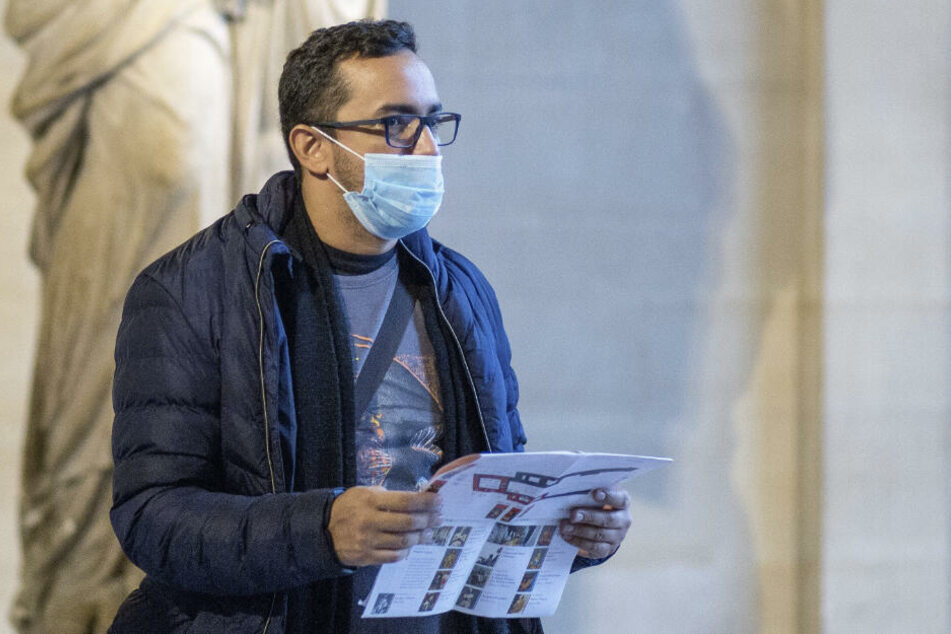 Ein Mann mit einer Schutzmaske besucht das Kunstmuseum Louvre.