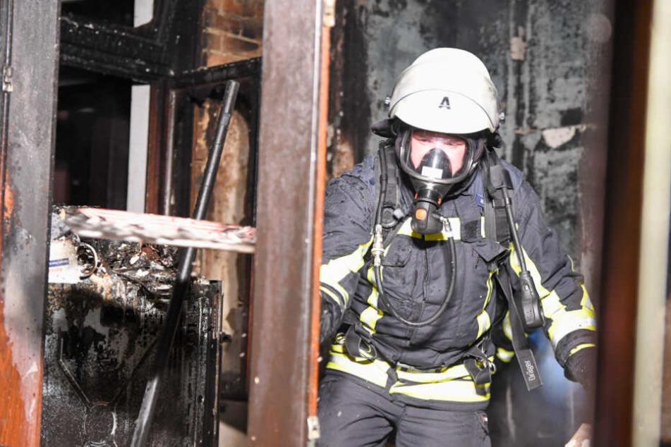 Ein Feuerwehrmann steht in dem ausgebrannten Zimmer.