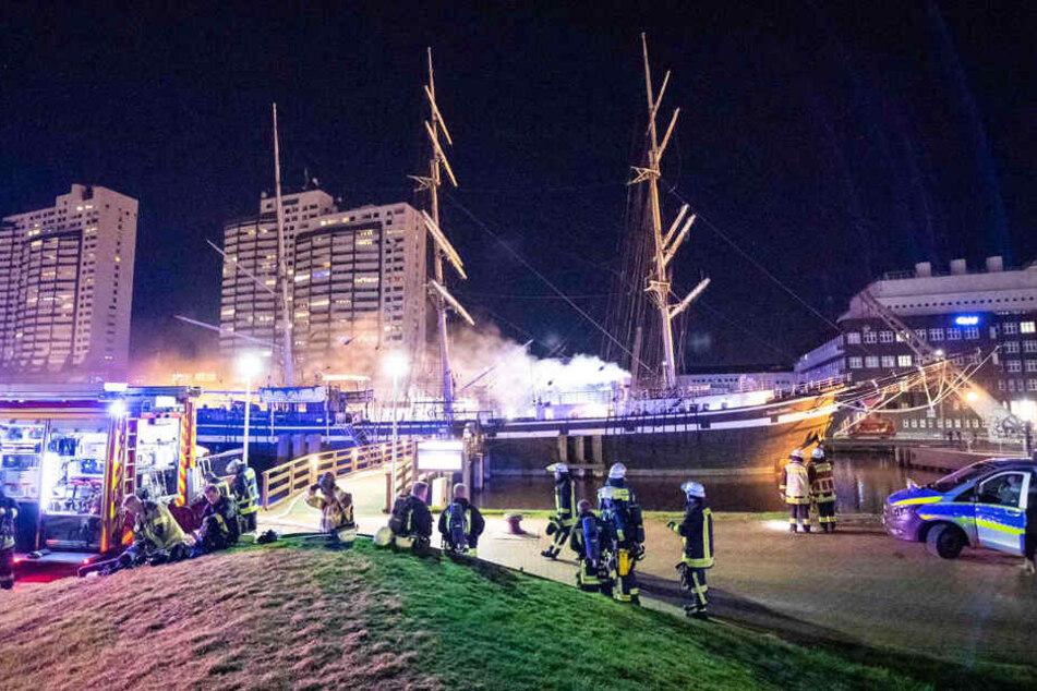 """Rauch steigt aus dem Schiff """"Seute Deern"""" auf. Feuerwehrleute bekämpfen den Brand."""