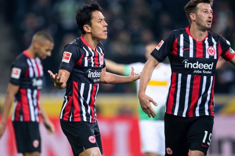 Makoto Hasebe (M.) und David Abraham (r.) werden der Eintracht wohl nach der kommenden Saison nicht mehr zur Verfügung stehen (Archivbild).