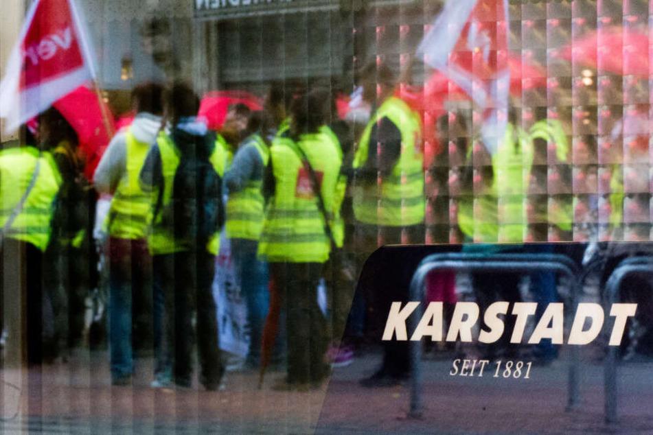 Streikende Mitarbeiter spiegeln sich im Schaufenster einer Karstadt Filiale. (Archivbild)