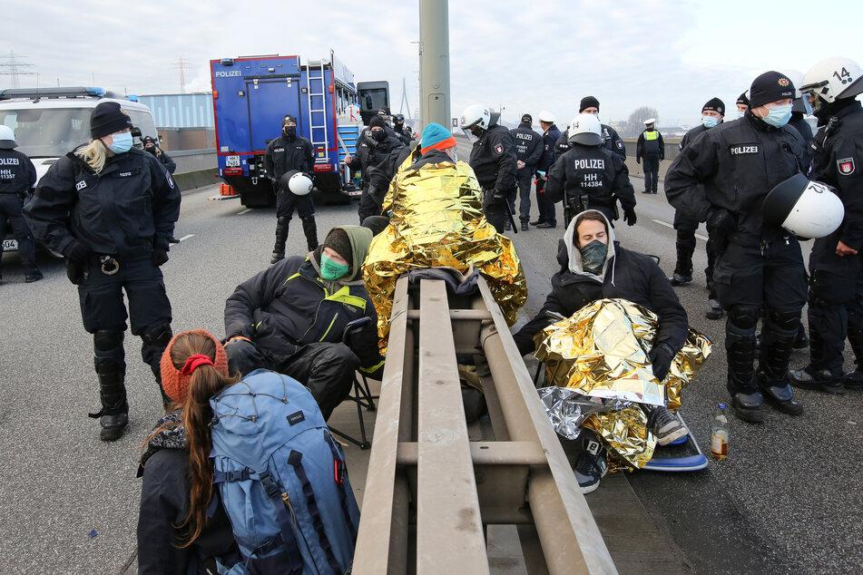 Polizisten stehen hinter Aktivisten im Hamburger Hafen.