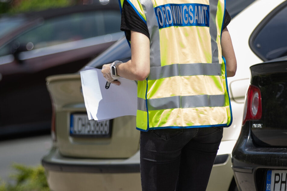Eine Mitarbeiterin des Ordnungsamtes passiert ein Auto mit rumänischem EU-Kennzeichen. Beim Schlachtereibetrieb Tönnies in Rheda-Wiedenbrück sind seit Anfang der Woche mehrere hundert Mitarbeiter positiv auf das Coronavirus getestet worden. In dem Unternehmen arbeiten viele Menschen aus Bulgarien und Rumänien.