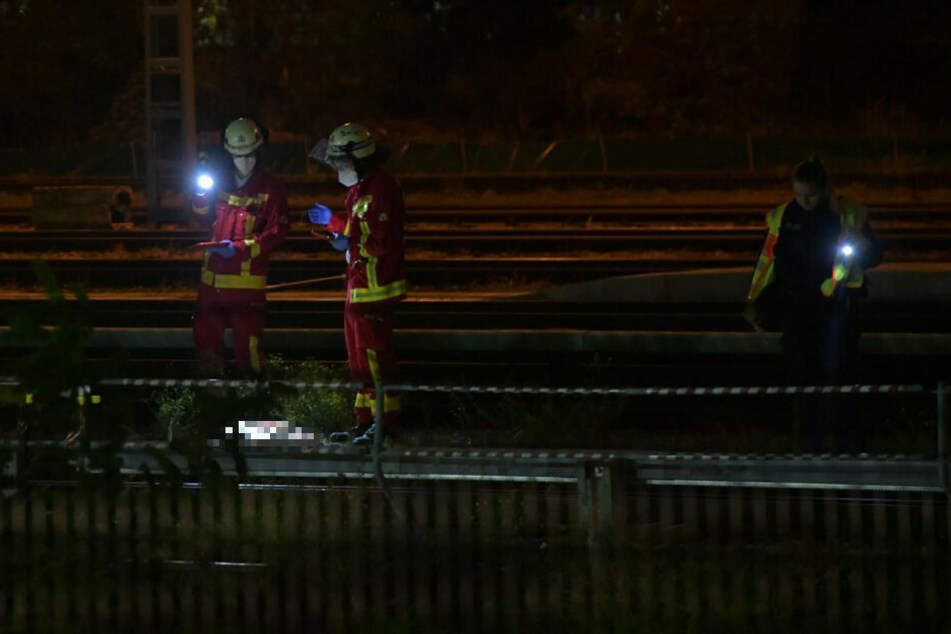 Mitarbeiter der Feuerwehr untersuchen den Leichnam. Eine Polizistin sucht währenddessen die Gleise ab.