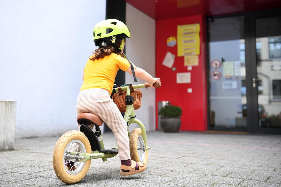 Ein kleines Mädchen rollt mit ihrem Laufrad zum Eingang einer Kindertagesstätte.