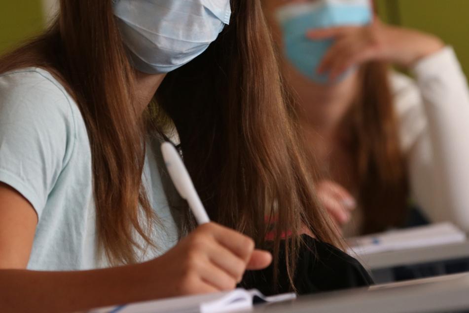 Mit Maske im Unterricht: Für Schüler in München wird das aufgrund der gestiegenen Zahlen noch länger Realität bleiben. (Symbolbild)