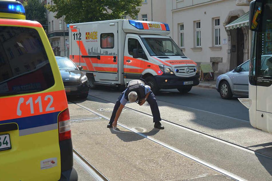 Ein Polizeibeamter markiert Spuren des Zusammenstoßes auf der Gorkistraße.