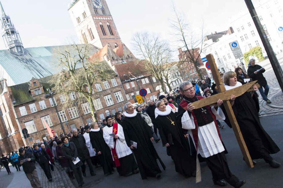 Teilnehmer tragen ein Holzkreuz bei der Begehung des ökumenischen Kreuzwegs, der als der älteste in Deutschland gilt.
