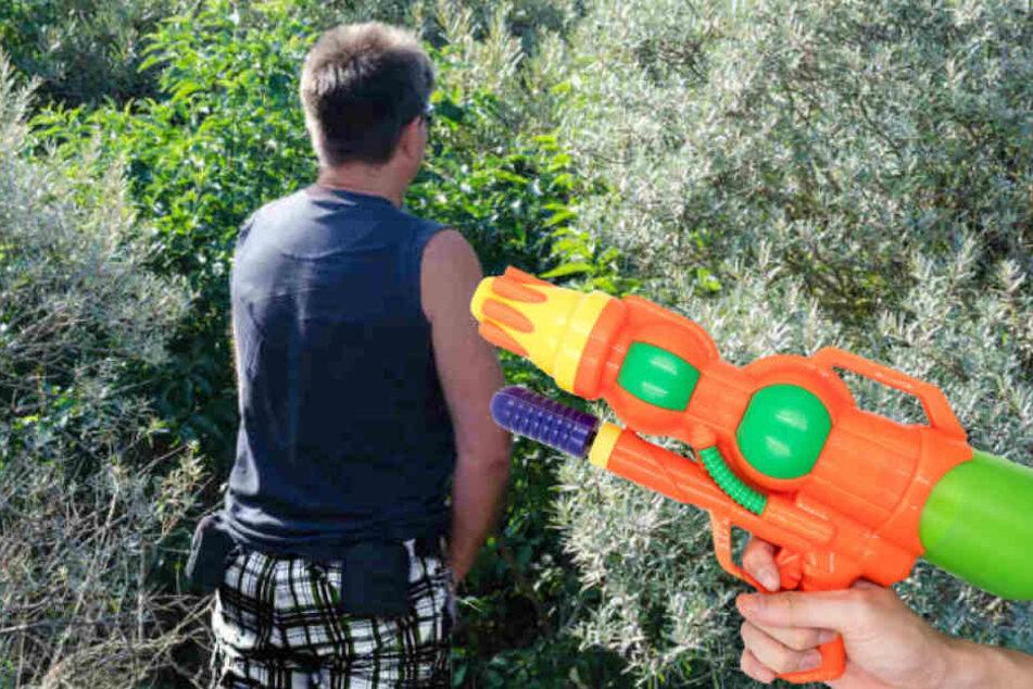 Erst pinkelte der Mann in die Wasserpistole, dann bespritzte er den Teenager. (Bildmontage)