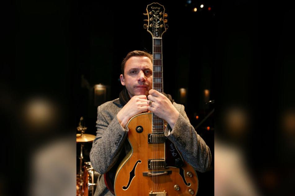 Der Musiker Rocko Schamoni sitzt mit seiner Gitarre auf einer Hamburger Kabarett-Bühne.