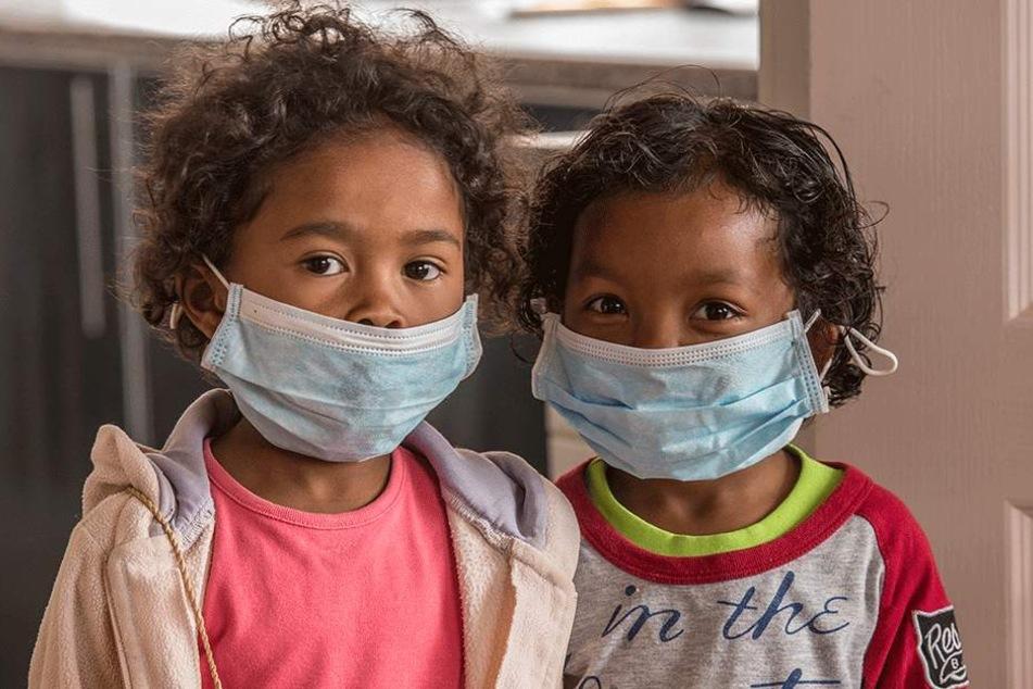 Kinder werden mit Mundschutz vor der tödlichen Pest geschützt.