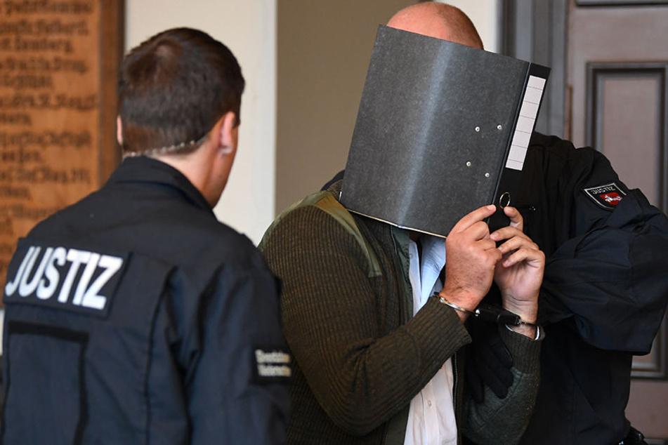 Der 32-jährige Angeklagte Kaire M. verdeckte bei Prozessbeginn sein Gesicht mit einem Aktenordner.