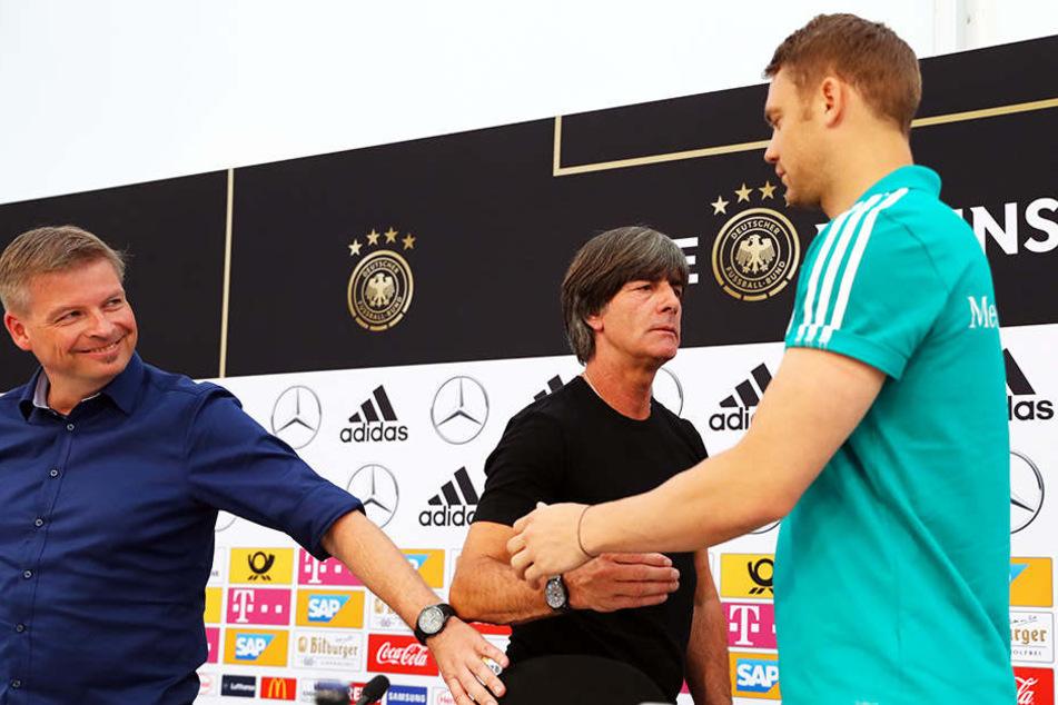Abklatschen: Torwart Manuel Neuer (r.) und Bundestrainer Joachim Löw (m.) mit DFB-Pressesprecher Jens Grittner (l.).
