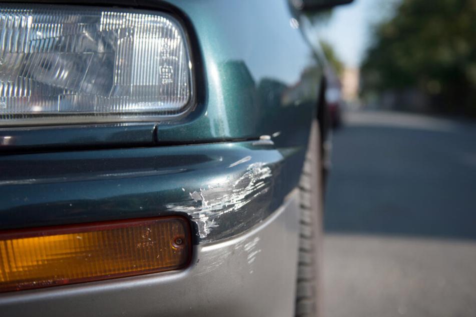 Am Stoßfänger eines geparkten Autos sind Spuren eines Unfalls zu sehen (Symbolbild).