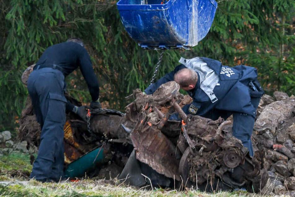 Einsatzkräfte der Polizei heben mit einem Kran ein Auto aus einem möglichen Ablageort einer Mädchenleiche.