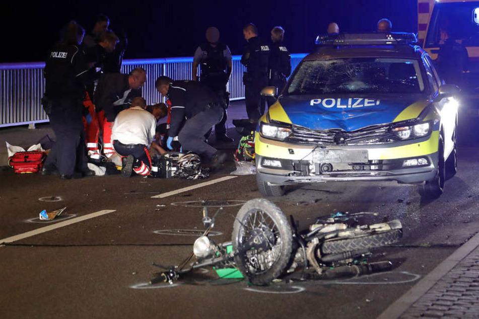 Der 17-jährige Moped-Fahrer wird an der Unfallstelle versorgt. Das Polizeiauto und die Simson sind schwer beschädigt.